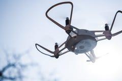 Zangão de Quadcopter que paira em um céu azul brilhante imagens de stock