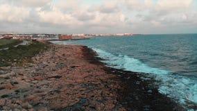 Zangão disparado da costa rochosa verde bonita com o trajeto pedestre estreito e ondas de oceano enormes que colidem em penhascos video estoque