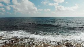 Zangão disparado das ondas de oceano que batem a praia rochosa Vista aérea das ondas do mar que espirram contra a praia filme