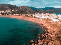 Zangão disparado de uma cidade pequena em Grécia com 2 praias imagem de stock royalty free