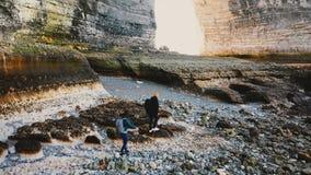 Zangão que segue o tiro da praia rochosa surpreendente de exploração do mar do seixo dos pares felizes do turista sob penhascos g video estoque
