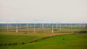 Zangão que voa lentamente longe da exploração agrícola da turbina do moinho de vento no campo nebuloso do outono, conceito re video estoque