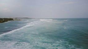Zangão que voa para a frente ao longo da vista calma da praia tropical exótica, ondas que lavam a costa que cria a textura do sea vídeos de arquivo