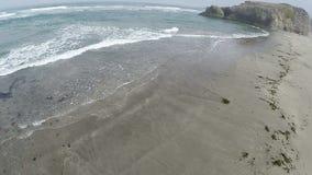Zangão que voa sobre a praia da areia para ondas e rochas de oceano vídeos de arquivo