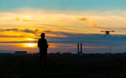 Zangão sobre a vila no por do sol nebuloso com seu piloto Foto de Stock Royalty Free
