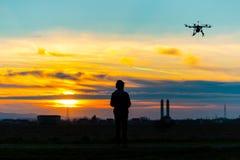Zangão sobre a vila no por do sol nebuloso com seu piloto Imagem de Stock