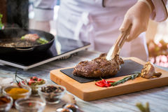 Zangen, die gekochtes Fleisch halten lizenzfreie stockfotografie