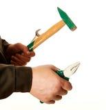 Zangen, ein Schlüssel und ein Hammer in den Händen des Arbeiters Stockfotografie
