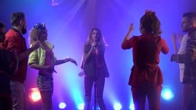 Zanger in een retro microfoon rond mensen die aan haar dansen die zingen Rook achtergrond Langzame Motie stock video