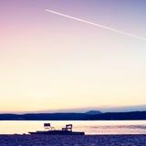 Zaniechana stara ośniedziała pedałowa łódź wtykał na piasku plaża Falisty poziom wody, wyspa na horyzoncie Jesień pogodna przy li Zdjęcia Royalty Free