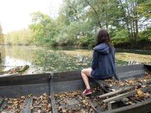 Zaniechane łodzie kłaść out na rzece z kobietami siedzi na one fotografia royalty free