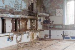 Zaniechany basen z zniszczonymi ścianami z balkonami i zegarem w opustoszałym Pripyt miasteczku w Chernobyl strefie obraz royalty free