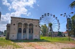 Zaniechany dom kultura i ośniedziały zaniechany Ferris toczymy wewnątrz parka rozrywki w Ochamchira, Abkhazia Zdjęcie Stock