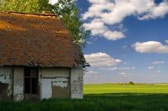 Zaniechany dom na wsi i rolniczy pola na pogodnym lecie Fotografia Stock
