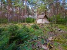 Zaniechany dom w sosnowym lesie pod łupkowego dachu pozycją obok łamanych rzędów ławki przeciw tłu obraz stock