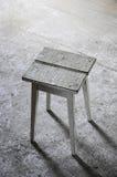 zaniechany miejsce z drewnianą stolec na popielatej podłoga Fotografia Royalty Free