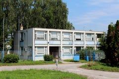 Zaniedbany budynek biurowy z obdrapanymi okno i drzwiami otaczającymi z uncut trawą i wysokimi drzewami w tle zdjęcia royalty free