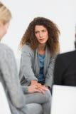 Zaniepokojona kobieta pociesza inny w rehab grupie przy terapią zdjęcie stock