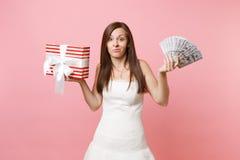 Zaniepokojona panny młodej kobieta w ślubnej sukni podesłania smirking rękach z plików udziałami dolary, gotówkowy pieniądze, cze zdjęcia royalty free