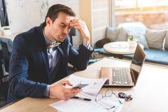 Zaniepokojony biznesmen patrzeje wiszącą ozdobę w biurze Obraz Stock