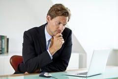 Zaniepokojony biznesmen przed laptopem Zdjęcie Stock