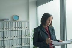 Zaniepokojony bizneswoman czyta biznesowego raport tapetuje w biurze fotografia royalty free
