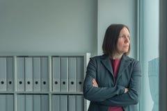 Zaniepokojony bizneswoman patrzeje z biurowego okno zdjęcia stock