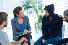 Zaniepokojony mężczyzna pociesza inny w rehab grupie Obraz Stock