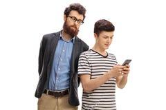 Zaniepokojony ojca zerkanie przy telefonem jego syn obrazy stock