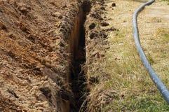 Zanja estrecha profunda para el tubo de agua Fotografía de archivo libre de regalías