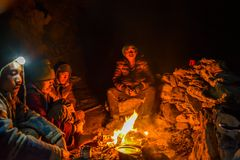 PORTERS HAVING WORMTH IN A CAVE DURING CHADAR TREK royalty free stock image