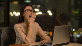 Zanudzająca kobieta pracuje na laptopie, wyczerpującym z nadgodziny, brak motywacja zbiory