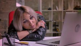 Zanudzająca śliczna caucasian blondynki kobieta jest łgarska na stole relaksującym i patrzeje laptopu ekran podczas gdy odizolowy