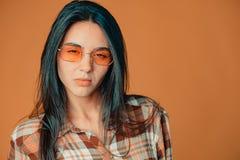 Zanudzająca śliczna młoda brunetki dziewczyna pokazuje nieufność na pomarańczowym tle obraz stock