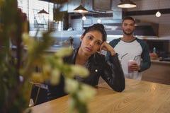Zanudzająca kobieta przy stołem z przyjaciela mienia milkshake szkłami w kawiarni obrazy stock