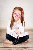 Zanudzająca młoda dziewczyna jest ubranym szkła i trzyma książkę Zdjęcie Stock