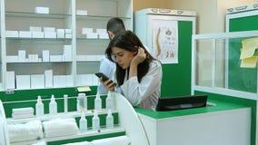 Zanudzająca młoda farmaceuta broqsing przez telefonu komórkowego przy miejscem pracy Obrazy Royalty Free