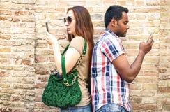 Zanudzająca multiracial para używa mobilnego mądrze telefon - nałóg jest zdjęcie stock