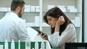 Zanudzający żeński farmaceuty use telefon komórkowy przy apteką Obrazy Royalty Free