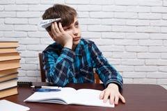 Zanudzający uczeń robi papieru samolotowi jego domowemu zadaniu Studiowań di obrazy stock