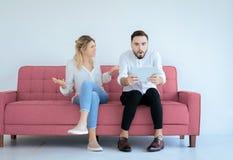 Zanudzający wpólnie i ignorowanie pary kochanka obsiadanie na kanapie w żywym pokoju przy domem, Rodzinni zagadnienia zdjęcie royalty free