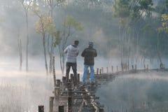 Zanurzający drzewa odbija na jeziorze z światłem, mgłą i ludźmi aktywnymi przy wschód słońca częścią 5 magii, zdjęcie stock