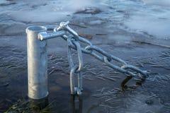Zanurzający słup z łańcuchem w lodowatej wodzie zdjęcia stock