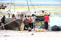 Zanzibar, local fishers near the boat to untangle the network. royalty free stock photo