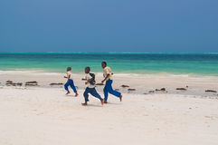 Zanzibar skolpojkar som kör längs stranden Arkivbild