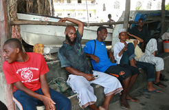 Zanzibar Stone Town, African Muslims black men rest in shade. Royalty Free Stock Images