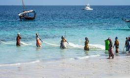 Zanzibar, Tanzania, Oost-Afrika - Juni 23, 2017: De Afrikaanse vrouwen van een visserijdorp vangen kleine vissen van de kust van royalty-vrije stock foto