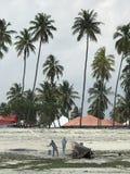 Men burn a boat on the beaches of Zanzibar. Zanzibar is a Tanzanian archipelago off the coast of East Africa. On its main island, Unguja, familiarly called Stock Photography