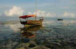 Zanzibar vessel. Lowtide in North Zanzibar leaves stranded vessel on coral Stock Photos