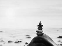 Zaokrąglony kolorowy kamienia stojak w postaci ostrosłupa dużego zaokrąglonego kamienia przy morzem Zdjęcia Stock